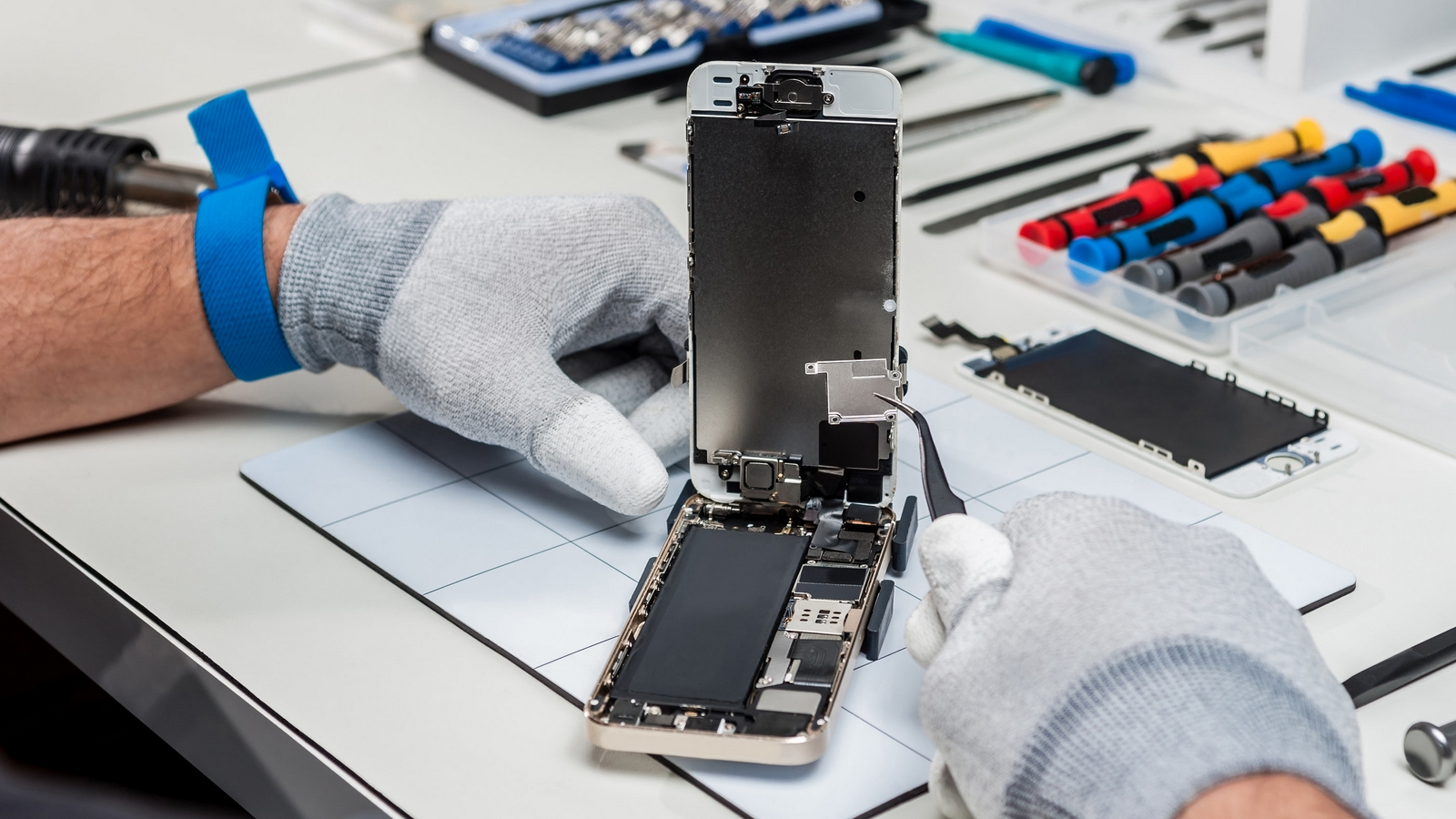 Technician replacing the screen of a used smartphone
